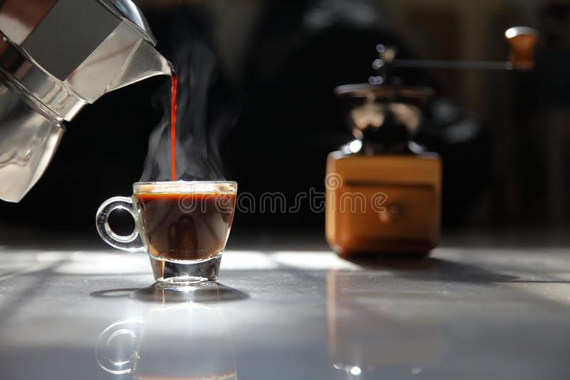 Traditional home brew espresso coffee pouring into a small cup with grinder on the dark background by the morning light with copy stock image