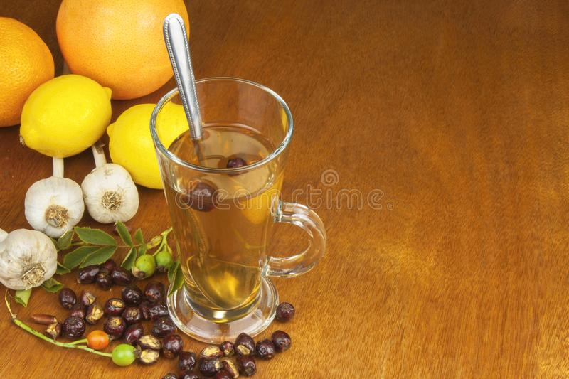 Traditional home treatment for colds and flu. Rosehip tea, garlic, honey and citrus. Hot tea with honey and lemon on a wooden tabletop. Home Pharmacy royalty free stock photography