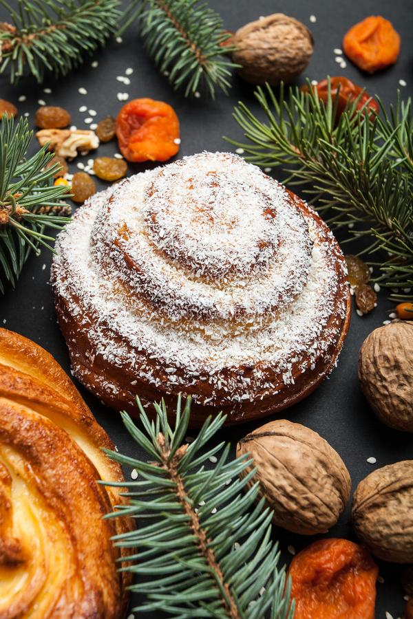 Traditional homemade bun in white glaze, a celebration of dessert with dried fruits in a Christmas tree tree ornaments royalty free stock images