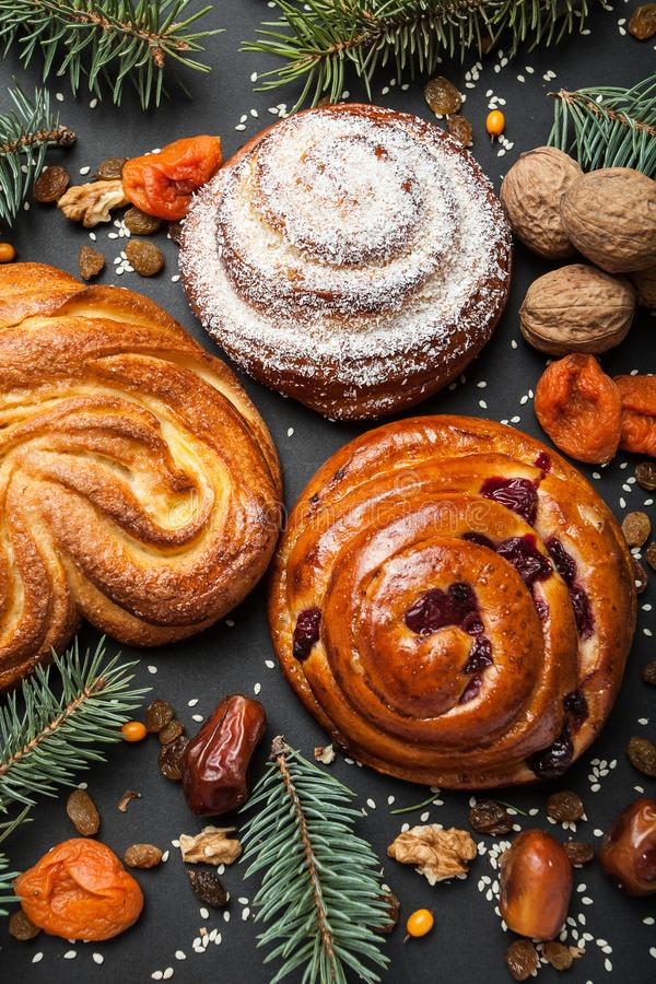 Traditional homemade buns with powdered sugar and dried fruits, Christmas tree branches, nuts. Vertically.  royalty free stock photography
