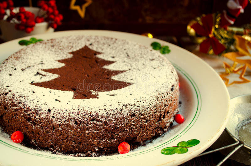 Traditional Homemade chocolate Christmas cake sprinkled with sugar powder, new year tree decoration. With snow stock image