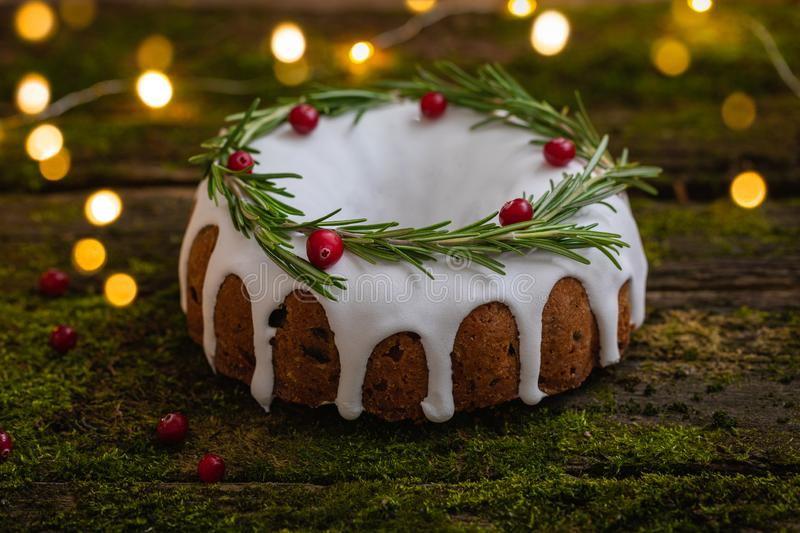 Traditional homemade Christmas fruit cake on the natural wooden background with moss. Decorated by cranberries and rosemary royalty free stock photo