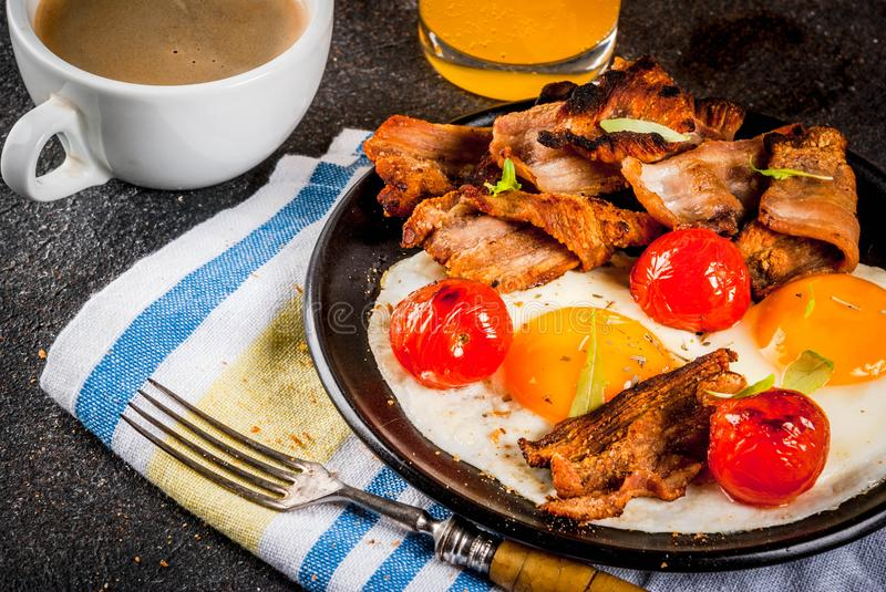 Traditional homemade english american breakfast, fried eggs, toasts, bacon, with coffee mug and orange juice dark background, top. View copy space royalty free stock photography