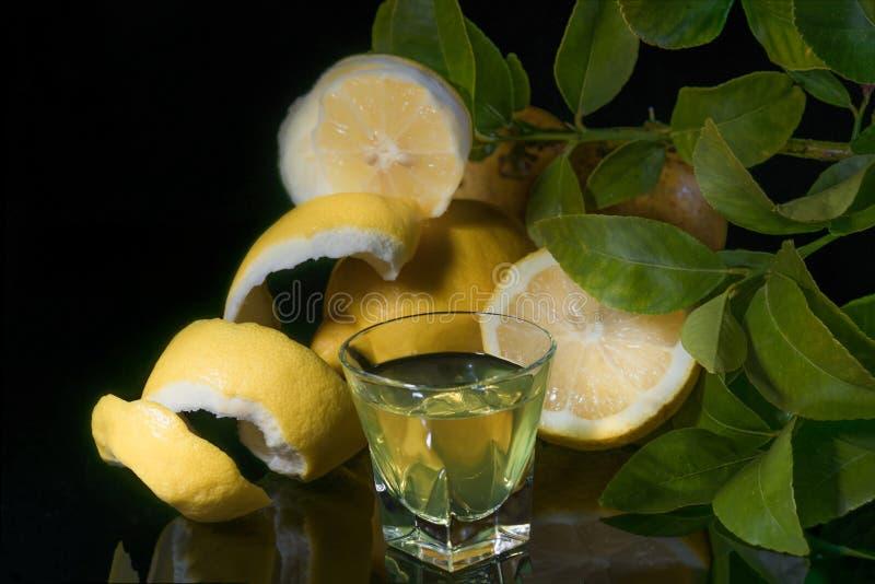 Traditional homemade lemon liqueur limoncello and fresh lemons on the black backgound royalty free stock image