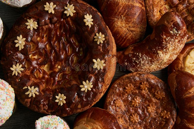 Traditional homemade Russian Easter baked goods. Kulichi, patties with cottage cheese, karavai and loaf cake with nuts on festive table background royalty free stock photos