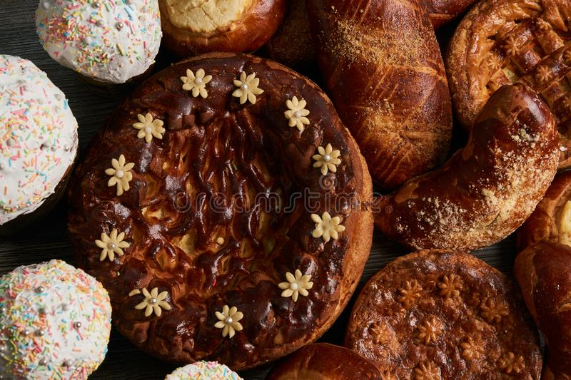 Traditional homemade Russian Easter baked goods. Kulichi, patties with cottage cheese, karavai and loaf cake with nuts on festive table background stock photos
