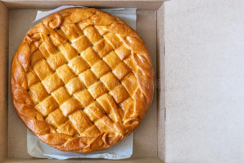 Traditional homemade rustic baked pie with seasonal fruit or meat filling in cardboard box. Fast food to go. Bakery delivery menu. Flat lay. Copyspace, dessert royalty free stock photo