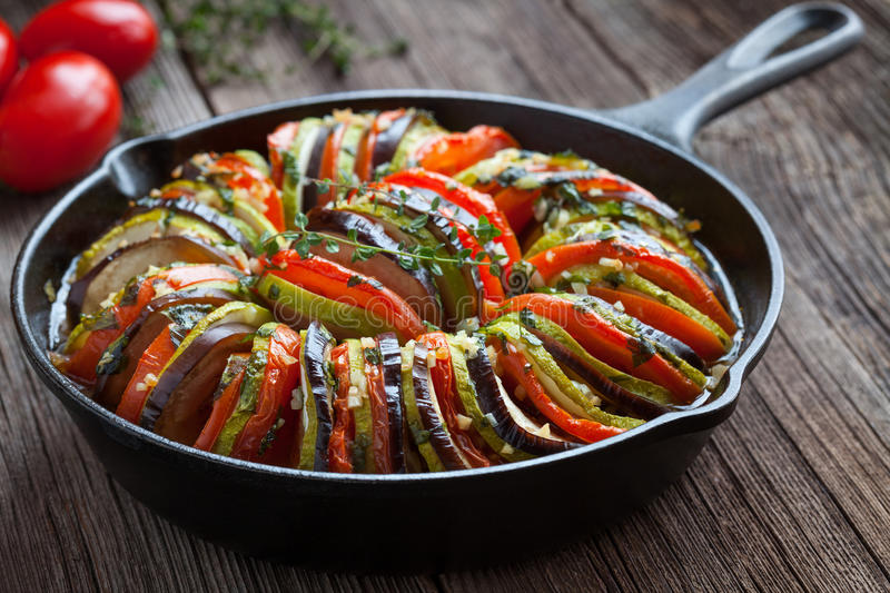 Traditional homemade vegetable ratatouille baked. In cast iron frying pan healthy diet french vegetarian food on vintage wooden table background. Rustic style stock photo