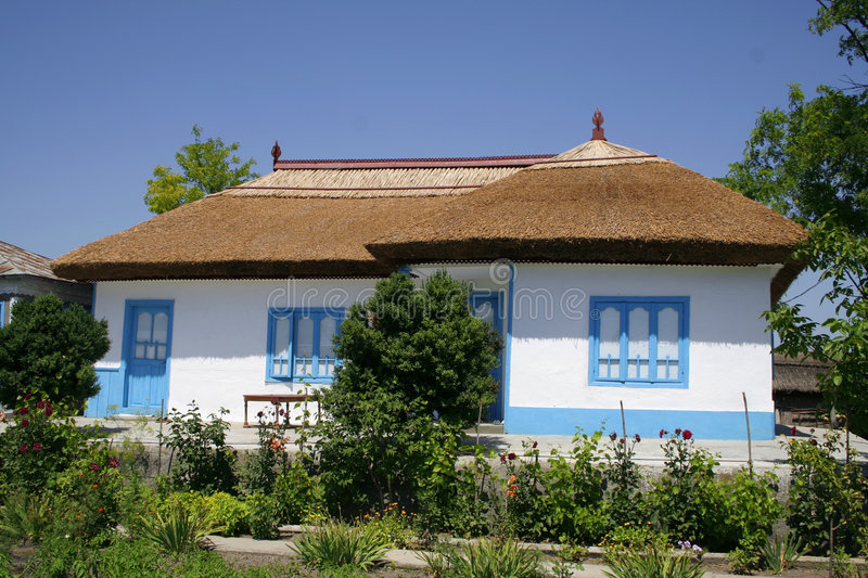 Traditional house from Danube Delta. White blue painted with reed roof royalty free stock photos