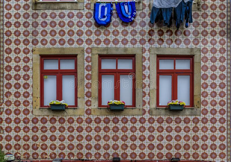 Traditional house facade decorated with ornate Portuguese azulejo tiles and laundry hanging outside in Porto, Portugal. Facades of traditional houses decorated royalty free stock images