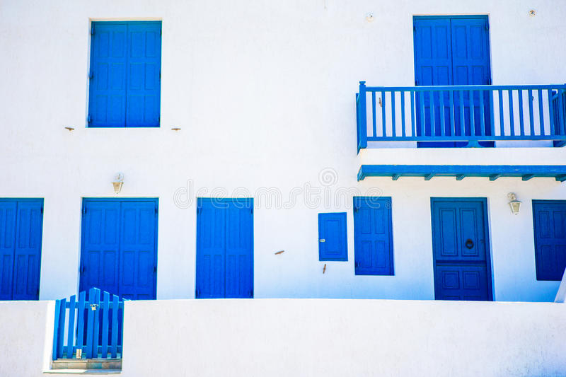 Traditional houses with blue doors and windows in the narrow streets of Mykonos, Greece. Traditional houses in the narrow streets of Mykonos, Greece stock photo