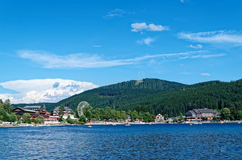 Traditional houses and ferris wheel on the promenade of the Titisee, Black Forest, Germany. Traditional houses and ferris wheel on the promenade of the Titi lake stock photo