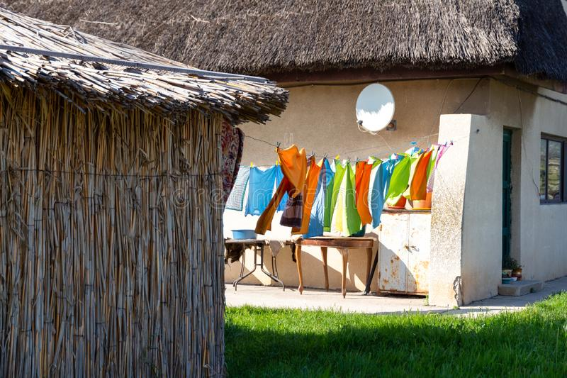 Traditional houses with reed roofs and washed clothes left out to dry on a wire in the wind, in a Romanian village near Black Sea stock photo