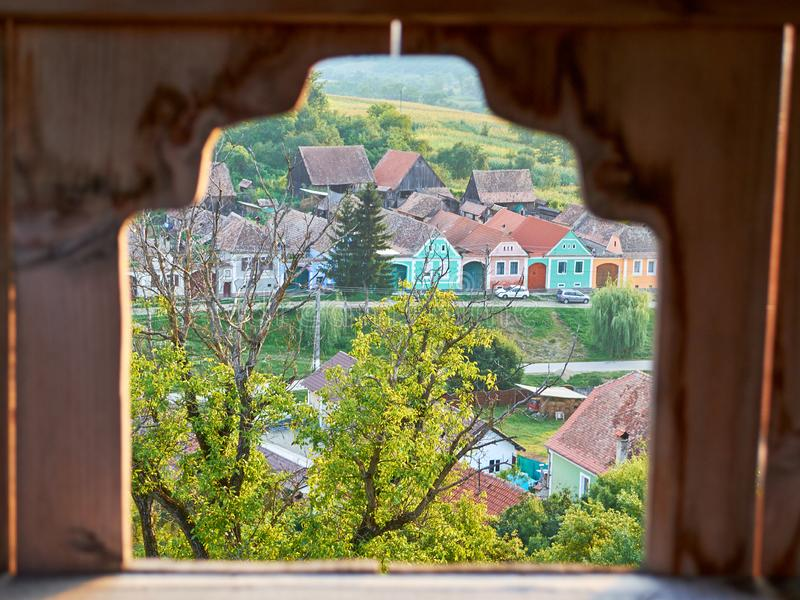 Traditional houses in Transylvania, Romania, seen through a frame in the Alma Vii fortified church stone wall stock photos