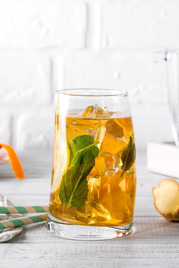 Traditional iced tea with lemon, ginger and ice in tall glasses on white background royalty free stock photos