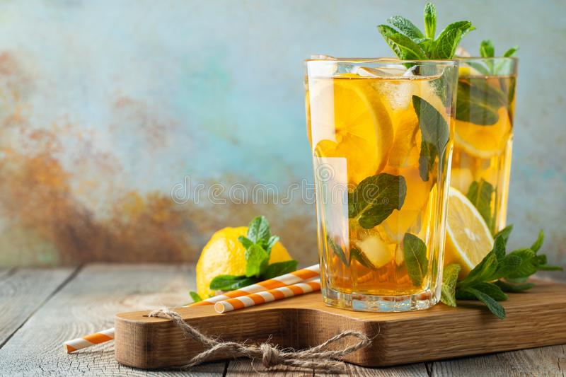 Traditional iced tea with lemon and ice in tall glasses on a wooden rustic table. With copy space stock photo