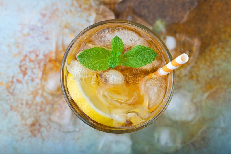 Traditional iced tea with lemon, mint and ice in tall glasses. A glass of refreshing summer drink on the old rusty background. Top royalty free stock images