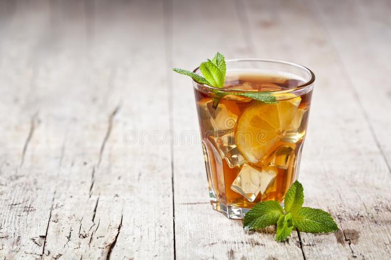 Traditional iced tea with lemon, mint leaves and ice in glass on rustic wooden table background stock photography