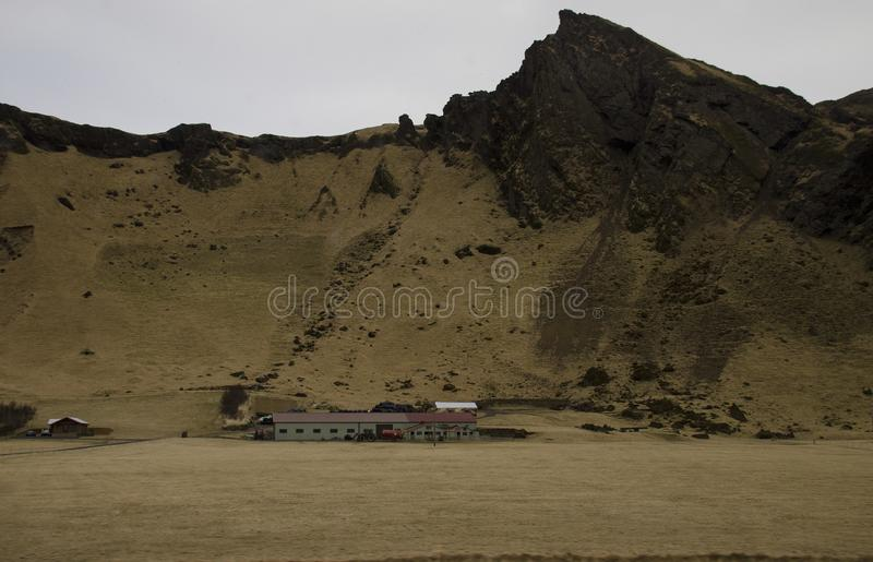 Traditional Icelandic farmhouses against the backdrop of a fantastic Icelandic landscape. Typical Icelandic landscape with houses against mountains in small stock image