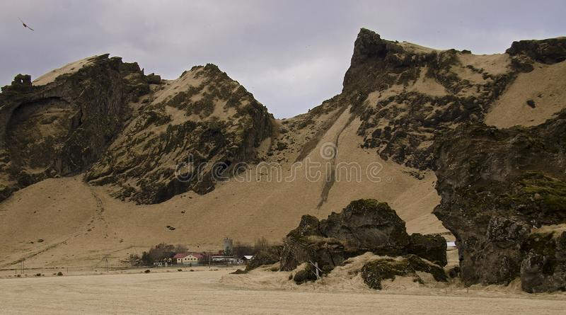 Traditional Icelandic farmhouses against the backdrop of a fantastic Icelandic landscape. Typical Icelandic landscape with houses against mountains in small royalty free stock photography