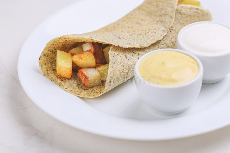 Vegetarian masala dosa with potato, chutney and sambar sauces royalty free stock images