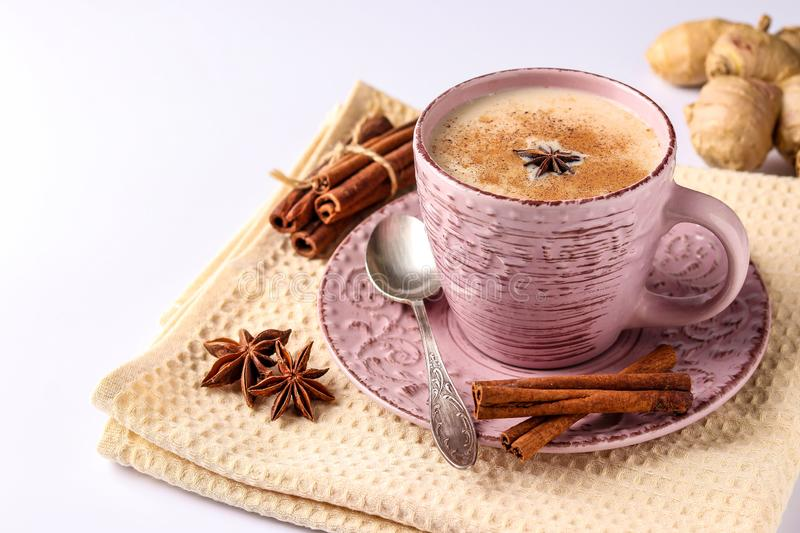 Traditional indian drink - masala tea with spices in pink cup on a white background, horizontal orientation, copy space. Close-up stock photos