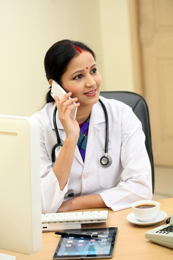 Traditional Indian female doctor talking on mobile phone stock photos