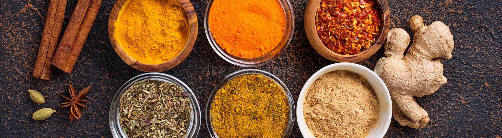Traditional Indian spices on rusty background. Traditional Indian spices. Turmeric, chili pepper, curry, ginger, dry herbs and saffron. Banner for design site royalty free stock image