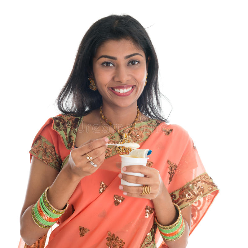 Traditional Indian woman eating yogurt stock image