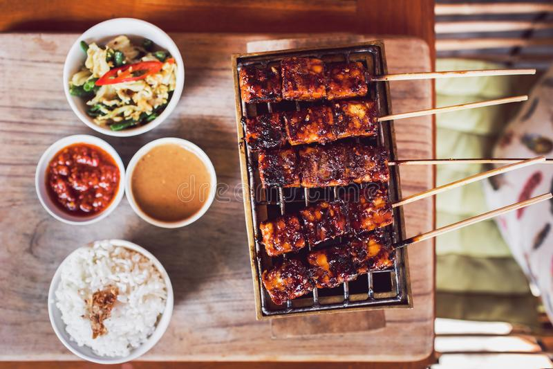 Grilled skewers tempe with sauces and white rice. Traditional indonesian grilled skewers of tempe with chili and peanut sauces and white rice. Vegan food royalty free stock images