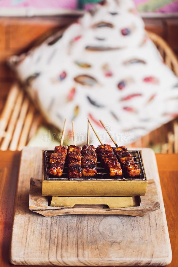 Grilled skewers of tempe on hot charcoals close up. Traditional indonesian grilled skewers of tempe on hot charcoals close up. Vegan food concept. Top view stock image