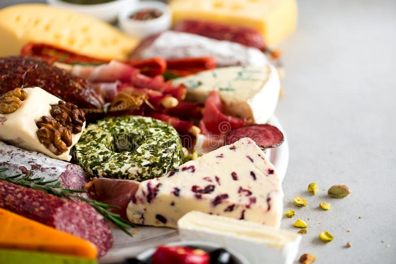 Traditional italian antipasto, cutting board with salami, cold smoked meat, prosciutto, ham, cheeses, olives, capers on royalty free stock image