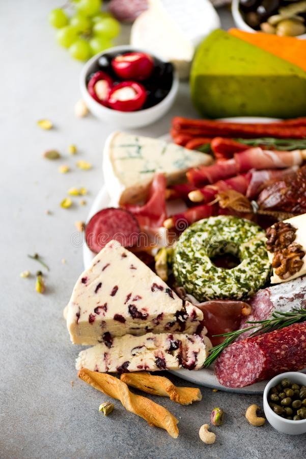 Traditional italian antipasto, cutting board with salami, cold smoked meat, prosciutto, ham, cheeses, olives, capers on royalty free stock photos