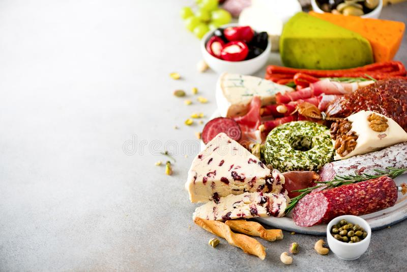 Traditional italian antipasto, cutting board with salami, cold smoked meat, prosciutto, ham, cheeses, olives, capers on royalty free stock photography