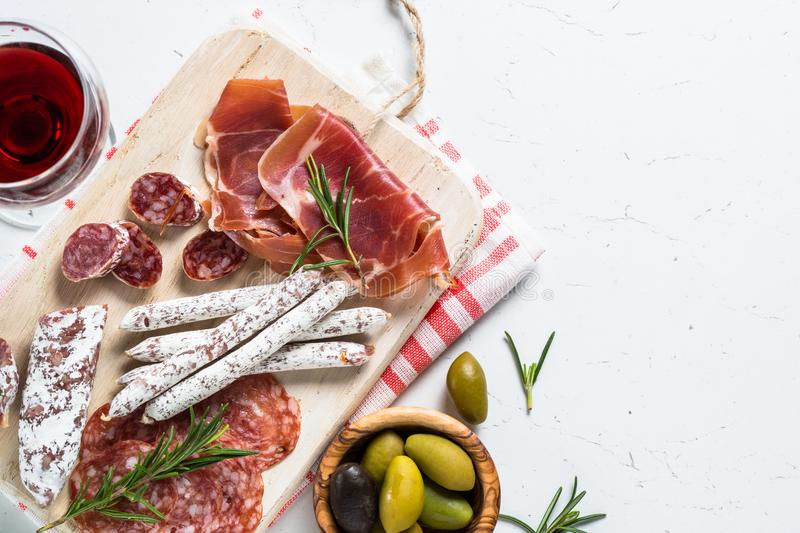Traditional italian antipasto on white. Traditional italian antipasto, sliced meat set with wine and olives on white table. Top view, copy space stock photos