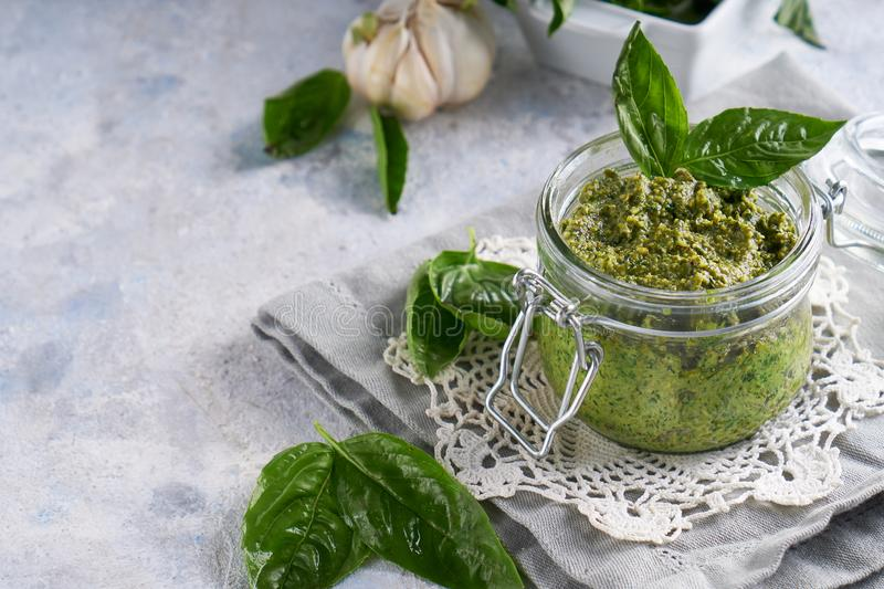 Traditional italian basil pesto sauce in a glass jar on a light stone table Copy space royalty free stock photos