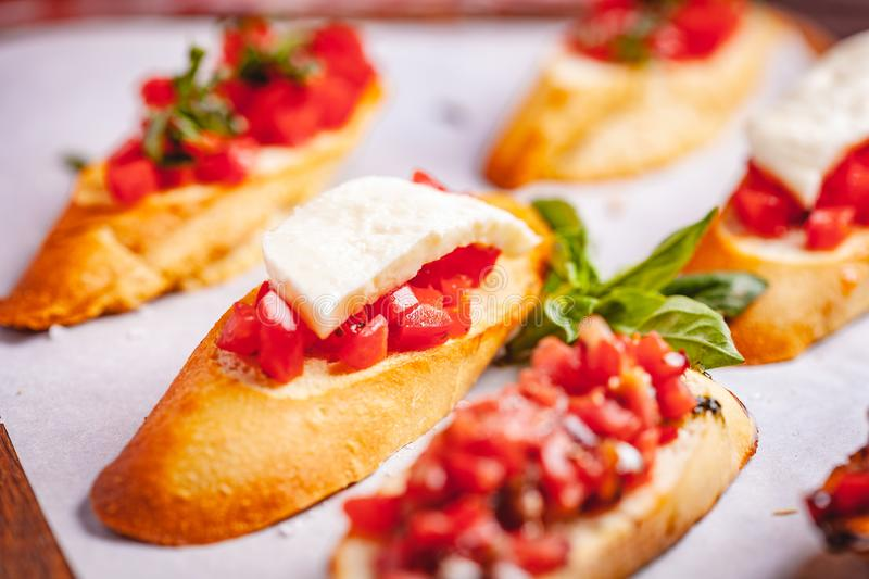 Traditional Italian bruschetta with cherry tomatoes, basil and mozzarella cheese on wooden cutting board. Close up royalty free stock photos