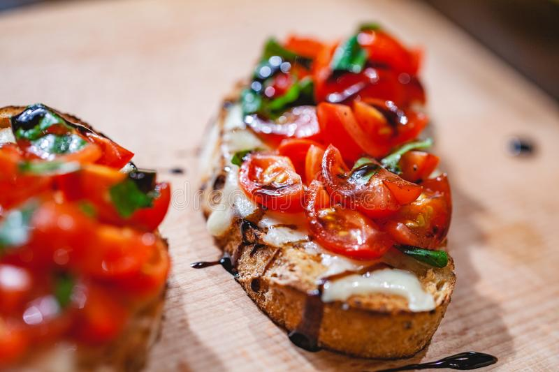 Traditional Italian bruschetta with cherry tomatoes, cheese, basil and balsamic vinegar on wooden board. Close up stock photo