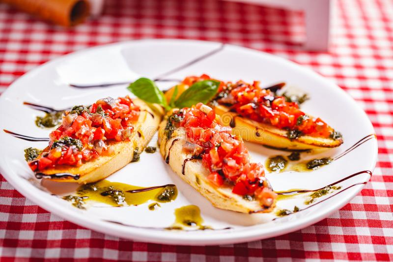 Traditional Italian bruschetta with cherry tomatoes, pesto sauce and balsamic vinegar on white plate. Close up royalty free stock photography