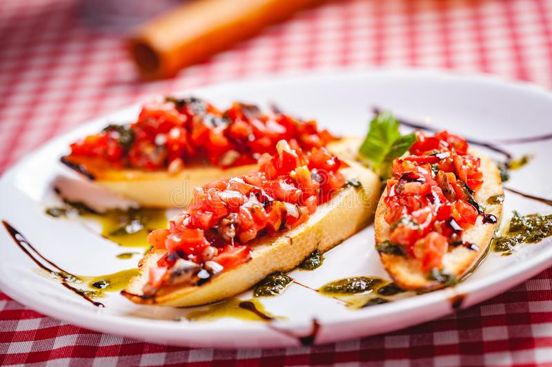 Traditional Italian bruschetta with cherry tomatoes, pesto sauce and balsamic vinegar on white plate. Close up stock images