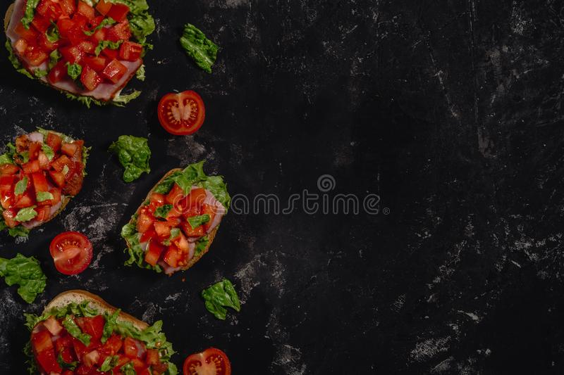 Traditional Italian Bruschetta with chopped tomatoes, mozzarella sauce, salad leaves and ham on a dark baton background. Traditional italian appetizer or snack royalty free stock photos