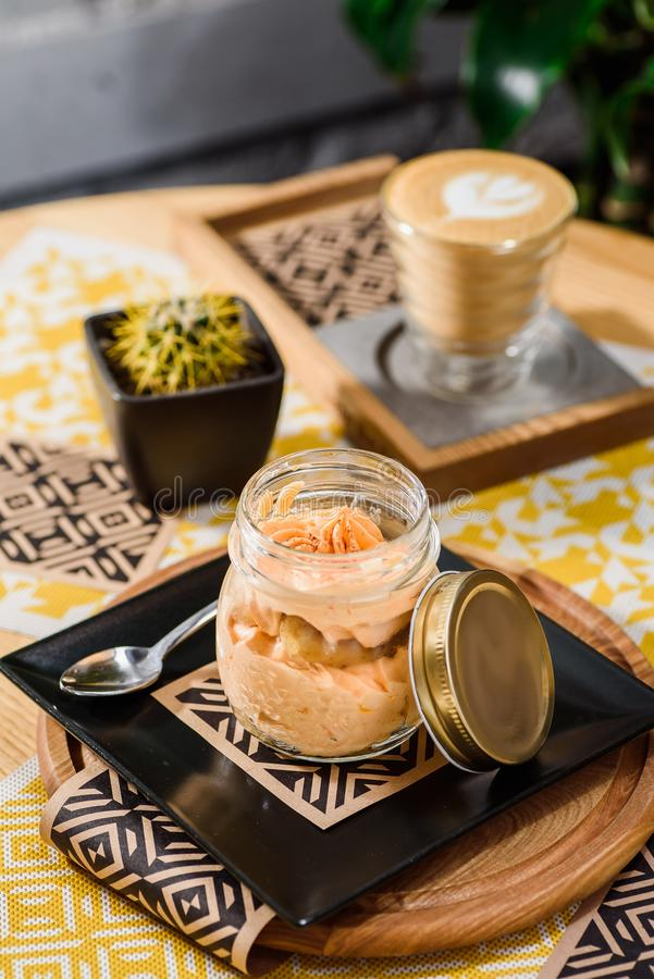 Traditional Italian dessert tiramisu in a jar on a wooden table in the restaurant stock photography