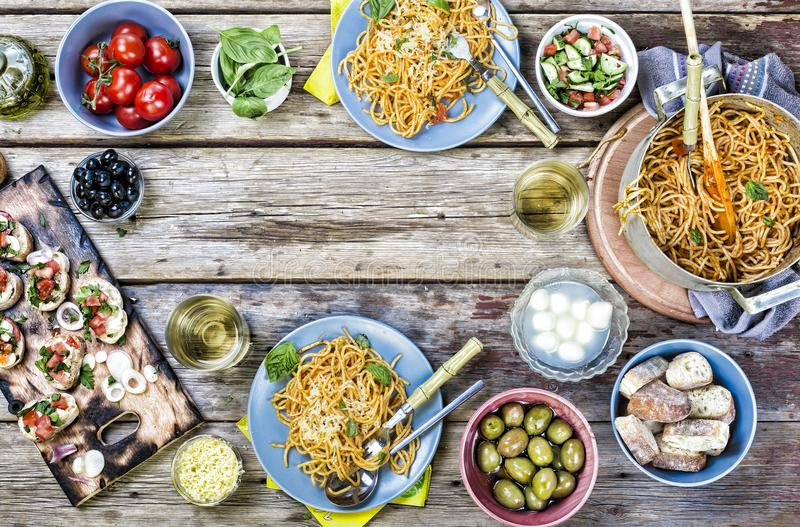 Italian food table, classic pasta, tomato sauce, eating outdoor, various European snacks,abundance of products, top view. copy spa royalty free stock photography