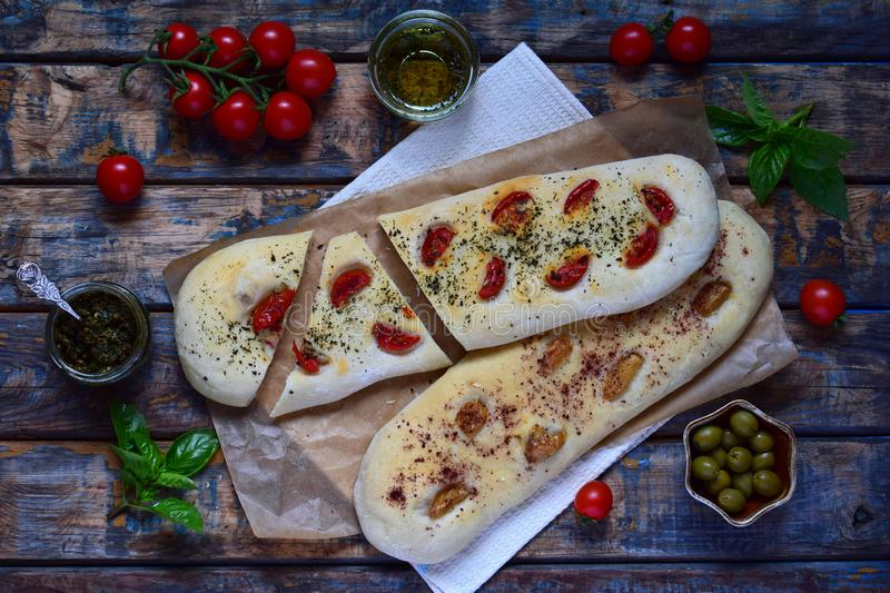 Traditional Italian Focaccia with tomatoes, basil, garlic and sumach. Homemade pastry. Flat bread. Organic flatbread. Rustic style. Traditional Italian Focaccia royalty free stock photo
