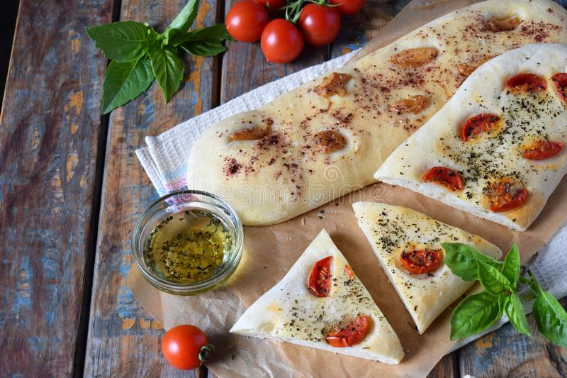 Traditional Italian Focaccia with tomatoes, basil, garlic and sumach. Homemade pastry. Flat bread. Organic flatbread. Rustic style. Traditional Italian Focaccia stock photography