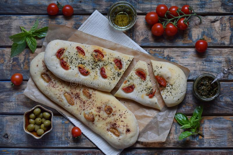 Traditional Italian Focaccia with tomatoes, basil, garlic and sumach. Homemade pastry. Flat bread. Organic flatbread. Rustic style. The traditional Italian royalty free stock photography