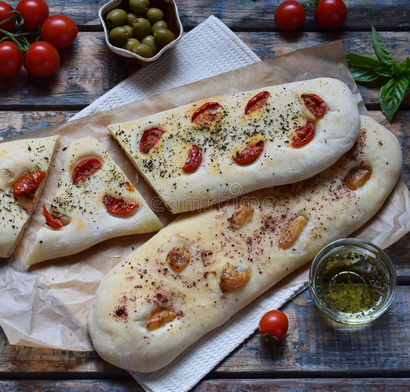 Traditional Italian Focaccia with tomatoes, basil, garlic and sumach. Homemade pastry. Flat bread. Organic flatbread. Rustic style. The traditional Italian stock images
