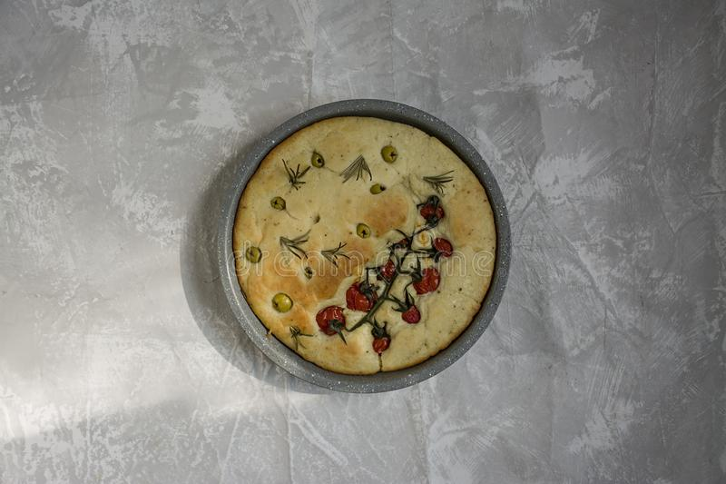 Traditional Italian focaccia with tomatoes, olives and rosemary. Baked focaccia in a baking tray. Round form. The process of royalty free stock photography