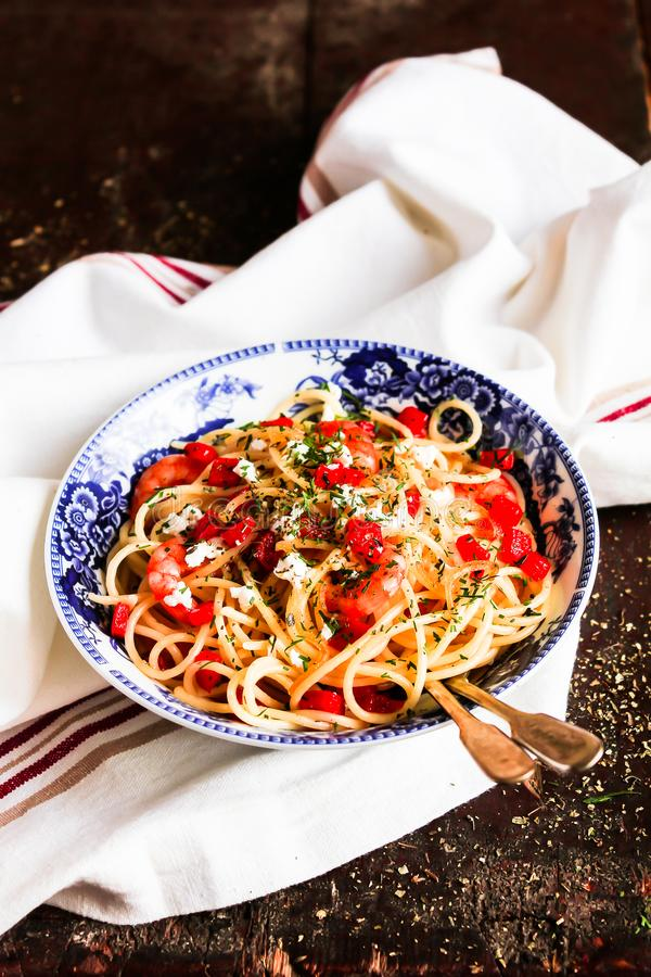 Traditional italian food. Bowl of homemade pasta spaghetti with fried shrimps or prawns, roasted red bell pepper, salted crumbled stock image