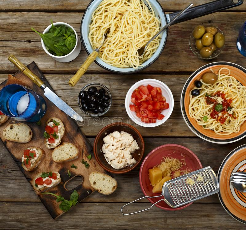 Traditional Italian food. Pasta spaghetti with tomato sauce, olives and garnish with wine on the wooden table royalty free stock photo